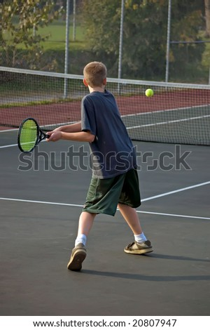 Teenage boy playing tennis, hitting a forehand - stock photo