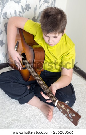 Teenage Boy plays an acoustic guitar while relaxing on a patio chair. - stock photo