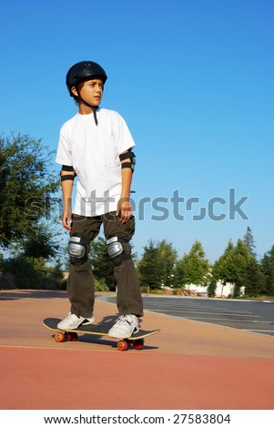 Teenage boy riding a skateboard on the sidewalk of a parking lot on a sunny day with blue sky and trees in the background.
