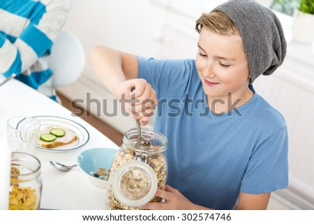 Teenage boy serving cereals out of a bottle at the breakfast table.