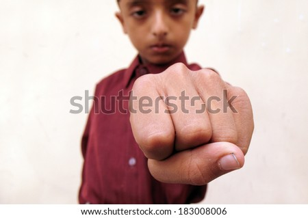Teenage boy showing punch in angry mood - stock photo