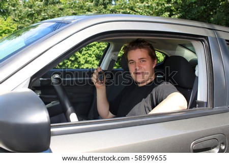 Teenage boy showing while holding a modern car key sitting behind the wheel. Conceptual for new car purchase, or new driver's lisence - stock photo