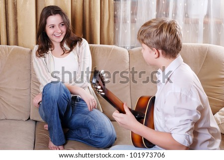 Teenage boy singing and playing on guitar for his girlfriend at home