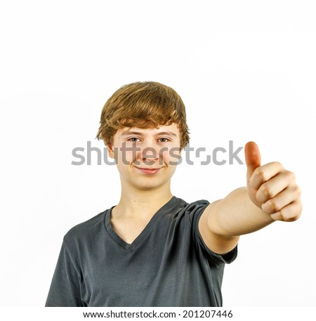 Teenage boy smiling showing thumbs up sign close up - stock photo