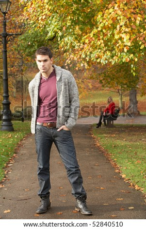 Teenage Boy Standing In Autumn Park With Female Figure On Bench In Background - stock photo