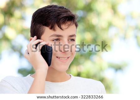 Teenage boy talking on the mobile in the street - stock photo
