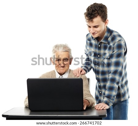Teenage boy teaching his grandfather how to use a laptop - stock photo