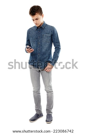 Teenage boy texting using his smartphone isolated on white, full body - stock photo