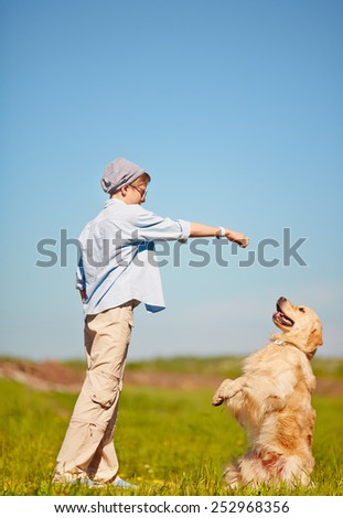 Teenage boy training his pet outdoors    - stock photo