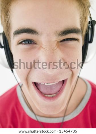 Teenage boy wearing headphones and smiling - stock photo