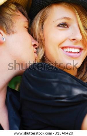 Teenage boy whispering secrets in his girlfriend's ear - stock photo