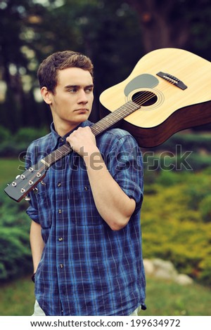 Teenage boy with acoustic guitar - stock photo