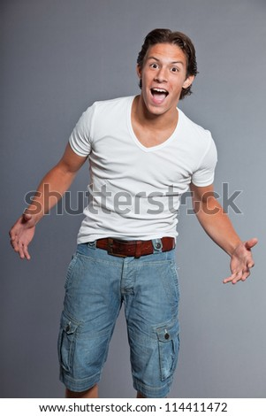 Teenage boy with brown hair and eyes. Wearing white t-shirt and blue shorts. Good looking. Casual wear. Expressions. Studio portrait isolated on grey background. - stock photo