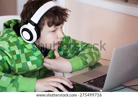 Teenage boy with headphones using laptop - stock photo