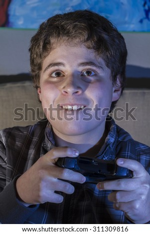 Teenage. boy with joystick playing computer game at home.