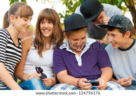 Teenage boys and girls having fun outdoor on beautiful spring day. - stock photo