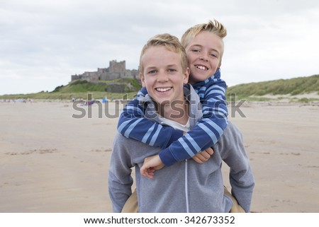 Teenage brothers at the beach with a castle in the background. They are wearing casual clothing and smiling at the camera.  - stock photo