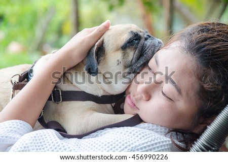 Teenage brunette girl playing hug and rest with her healthy young pug dog in the park