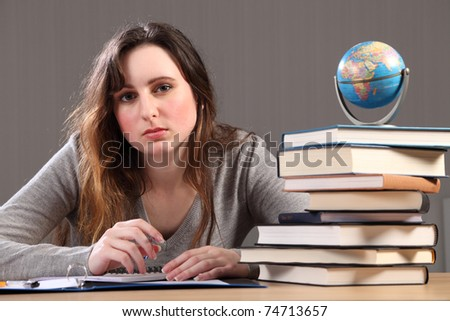 Teenage caucasian student girl at home, sitting to her desk studying geography with work books nearby and a globe of the world. - stock photo
