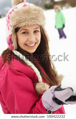 Teenage Couple Having Snowball Fight Wearing Fur Hats - stock photo