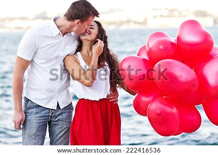 Teenage couple holding red baloons-hearts. valentine day - stock photo