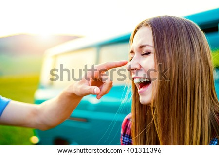 Teenage couple in love outside, man touching her nose - stock photo