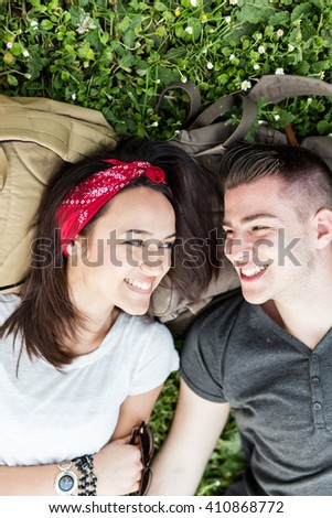 Teenage couple lying down on the grass. Depth of field, selective focus - stock photo