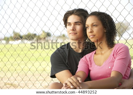 Teenage Couple Sitting In Playground - stock photo