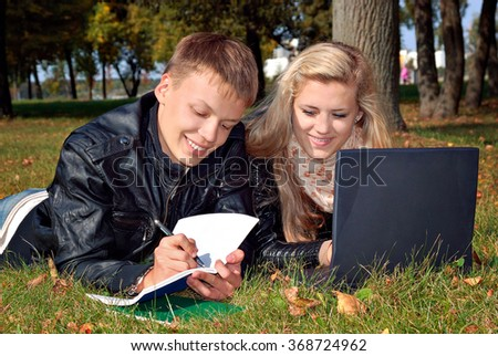teenage couple studying in the park with laptop, youth lifestyle and college - stock photo