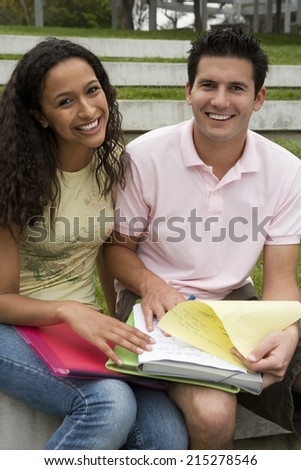 Teenage couple studying together, looking at notes, smiling, portrait - stock photo