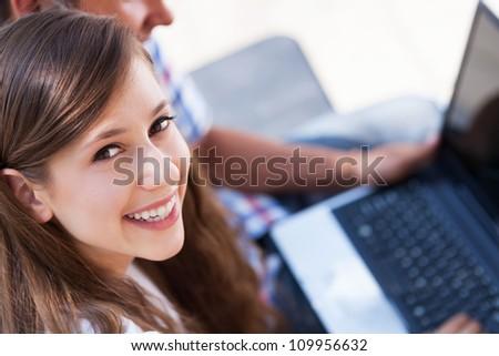 Teenage couple using laptop - stock photo