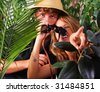 Teenage couple wearing safari hat with binoculars adventuring in the jungle - stock photo