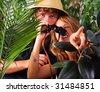 Teenage couple wearing safari hat with binoculars adventuring in the jungle - stock photo