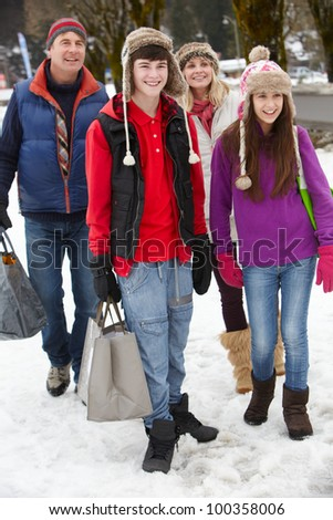 Teenage Family Carrying Shopping Walking Along Snowy Street - stock photo
