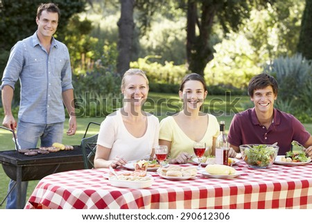 Teenage Family Enjoying Barbeque In Garden Together - stock photo