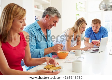 Teenage Family Having Breakfast In Kitchen With Laptop - stock photo