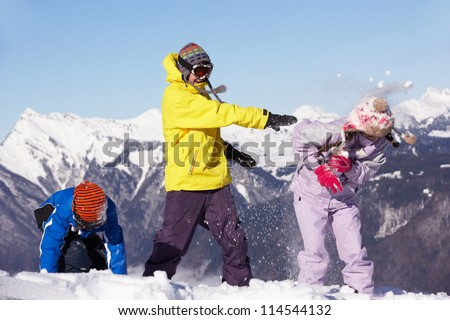 Teenage Family Having Snow Fight In Mountains - stock photo
