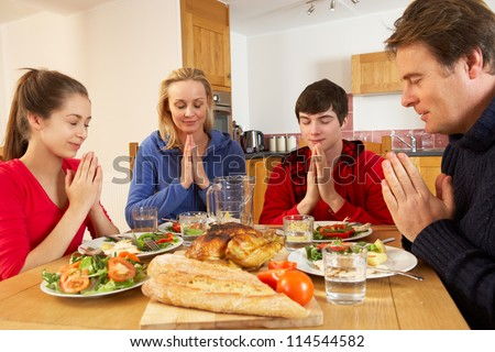 Teenage Family Saying Grace Before Eating Lunch Together In Kitchen - stock photo