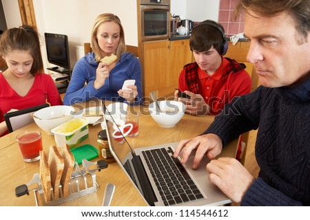 Teenage Family Using Gadgets Whilst Eating Breakfast Together In Kitchen - stock photo