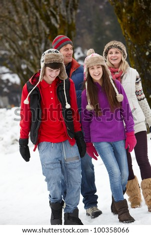 Teenage Family Walking Along Snowy Street In Ski Resort - stock photo