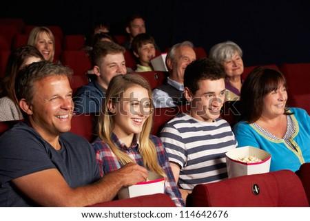 Teenage Family Watching Film In Cinema - stock photo