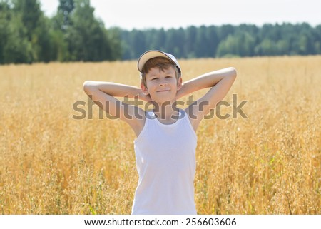 Teenage farmer standing among Avena sativa or common oat field - stock photo