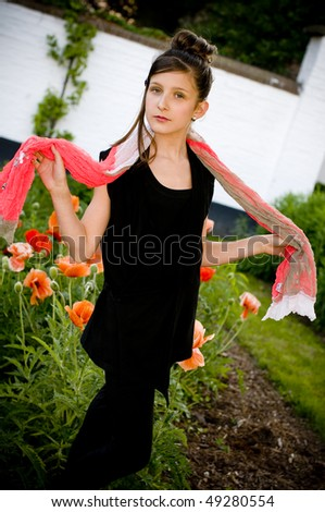 Teenage fashion girl with red scarf in a park with red poppies