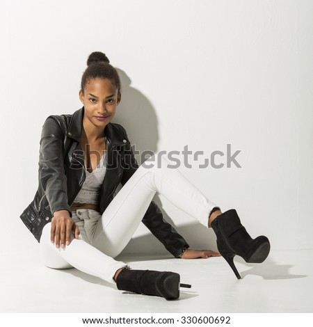 Teenage fashion model sitting on a white floor leaning towards a white wall. She is looking into the camera with a confident smile. - stock photo