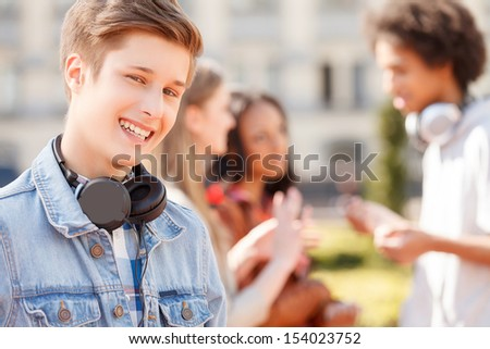 Teenage friends. Cheerful teenage boy smiling at camera while his friends talking on the background - stock photo