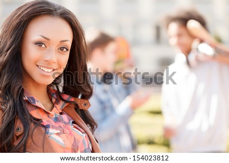Teenage friends. Cheerful teenage girl smiling at camera while her friends talking on the background - stock photo
