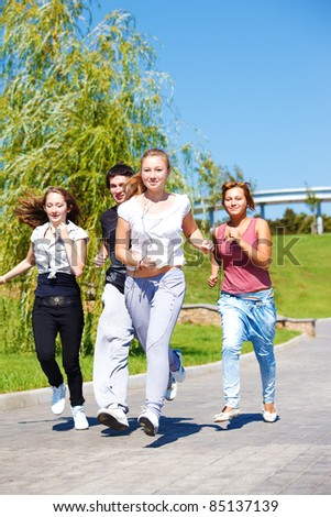 Teenage friends jogging in city park - stock photo