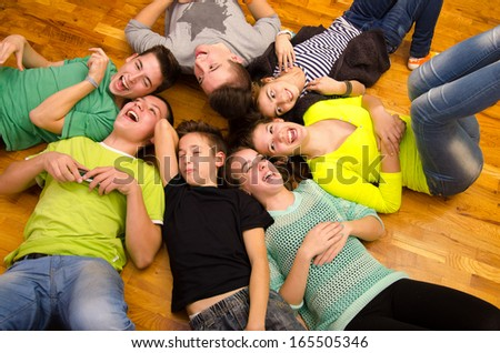 Teenage friends lying on the floor and laughing. - stock photo