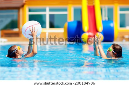 teenage friends playing with ball in the pool - stock photo