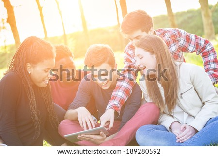 Teenage Friends using Digital Tablet at Park - stock photo